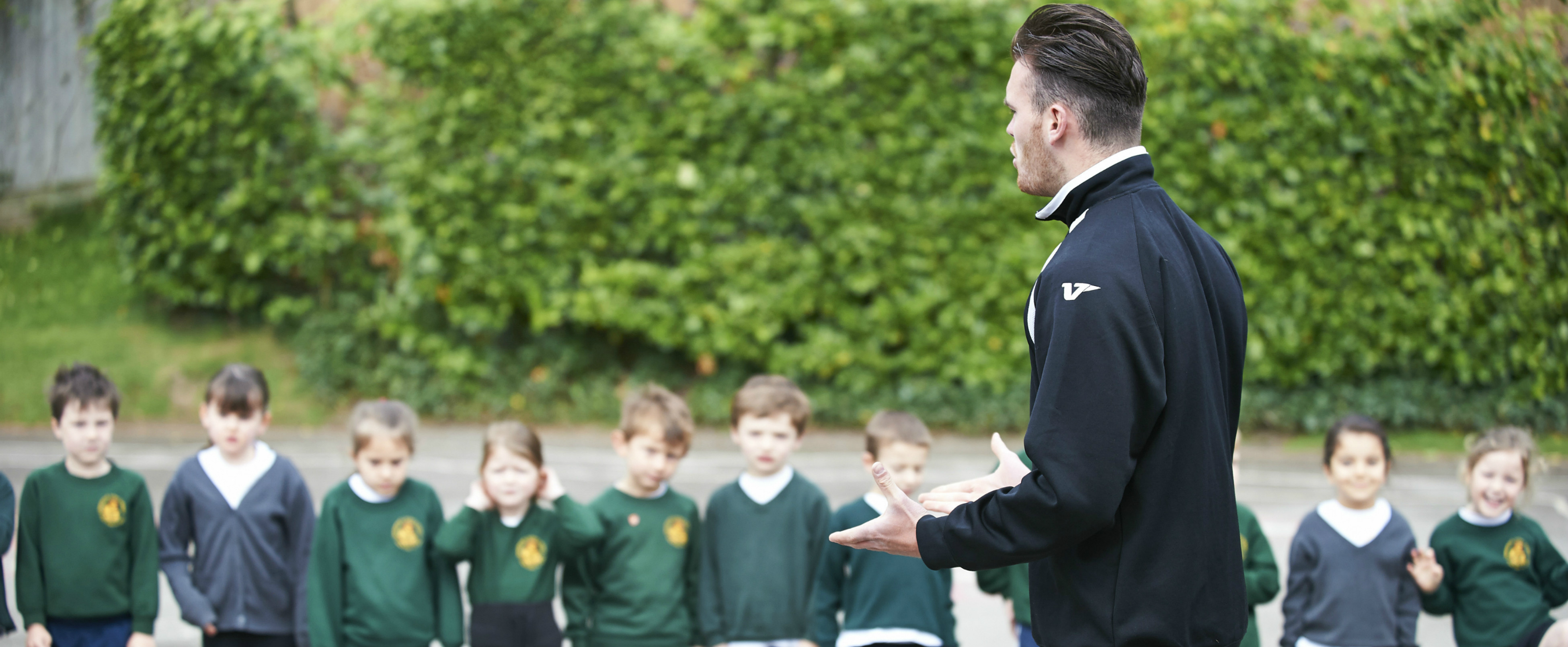 An SCL apprentice teaching a sports session at a local primary school