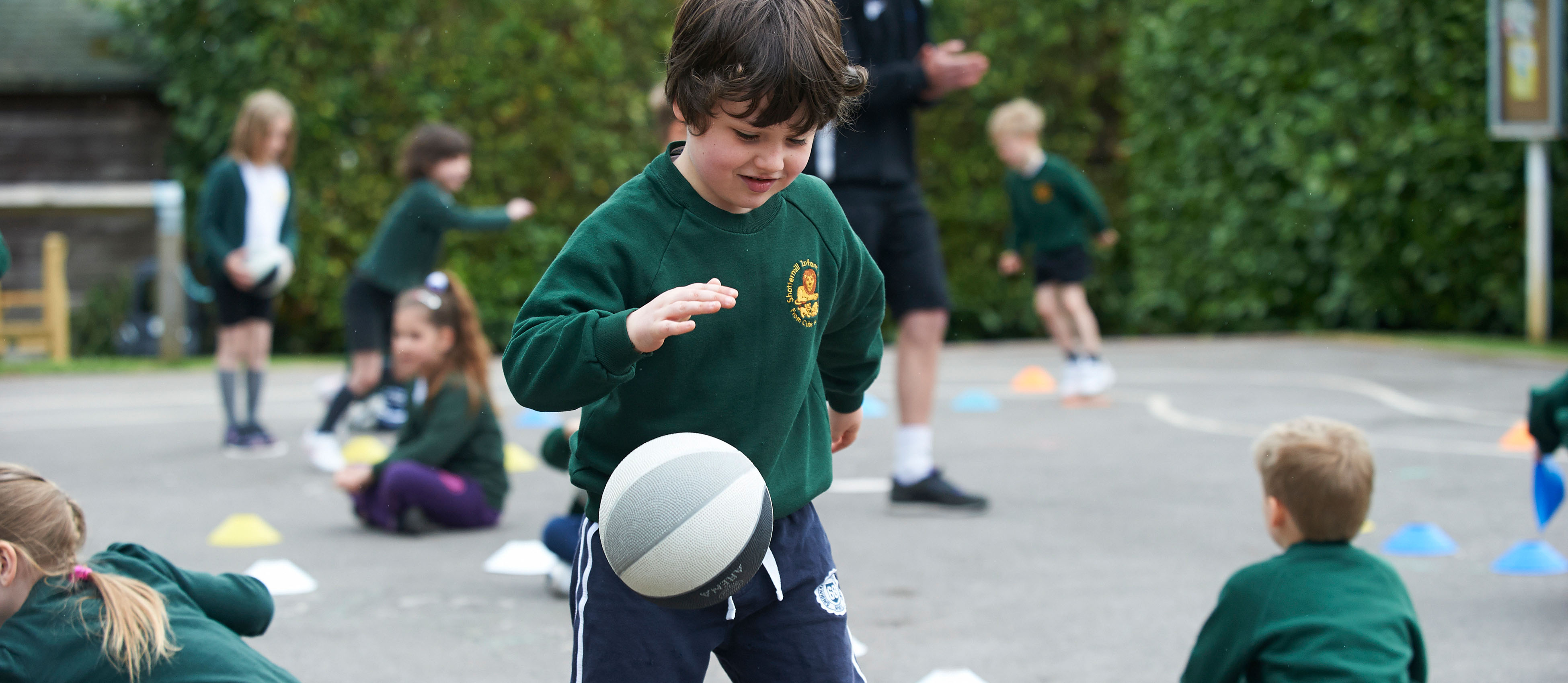 Primary school kids playing basketball at an SCL Lunchtime Club.