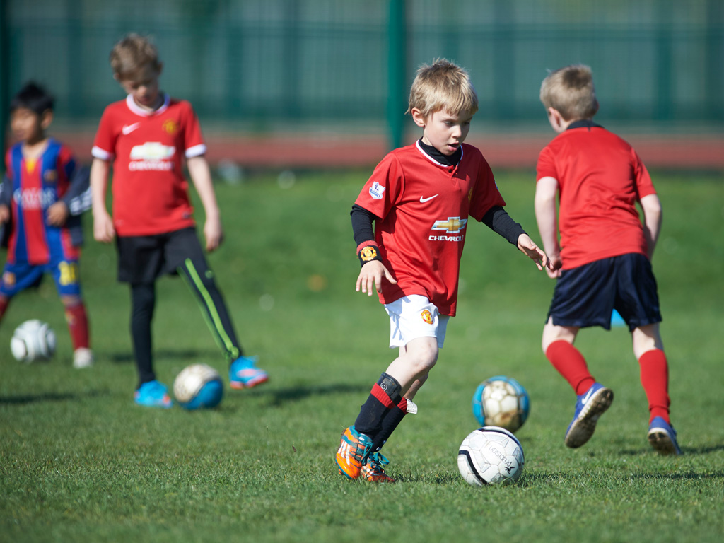 Kids aged 4 - 10 playing a football match at an SCL Saturday soccer session